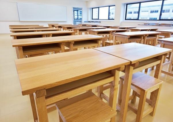 木製の机と椅子を備える書道室