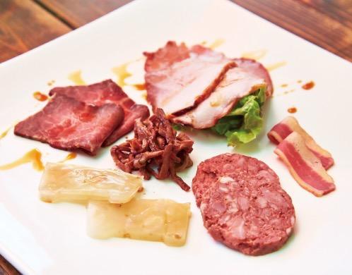 「前菜色々盛り合せ」(8500円・12000円コースの前菜5~6種盛り。仕入れの状況により一部変更あり)。手前から左回りで、アキレスの煮こごり、モモ肉のローストビーフ、自家製焼き豚、桜肉のベーコン、ひぞうを使った田舎風パテ、中心は食道網焼きのづけ