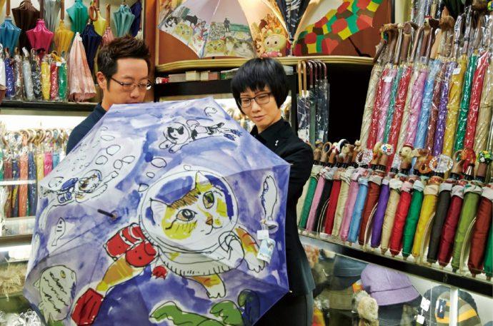 岡田久生さんと、おしゃれな猫たちが描かれた「マンハッタナーズ」の傘を広げて