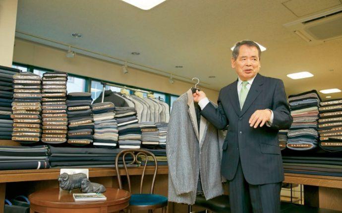 仮縫いのジャケットを手にする稲沢さん。着心地の良い柴田のジャケットは、一人の職人がほぼ手縫いで仕上げ、約6万針がスタンダード