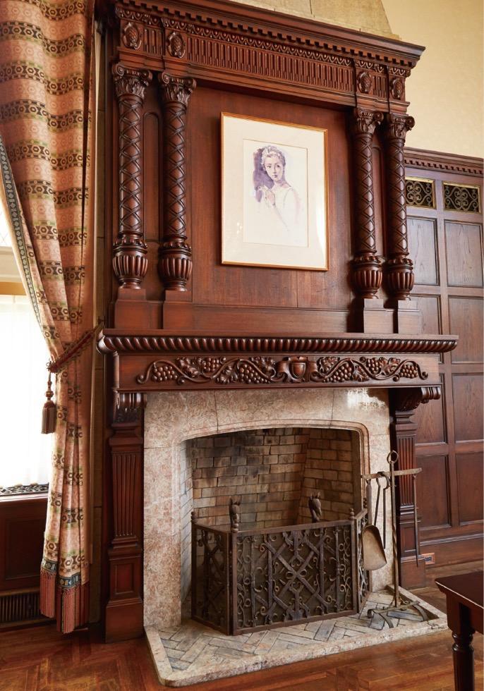 ゲストルーム正面中央の暖炉。上部には、丸柱とチーク材による優美な装飾がある