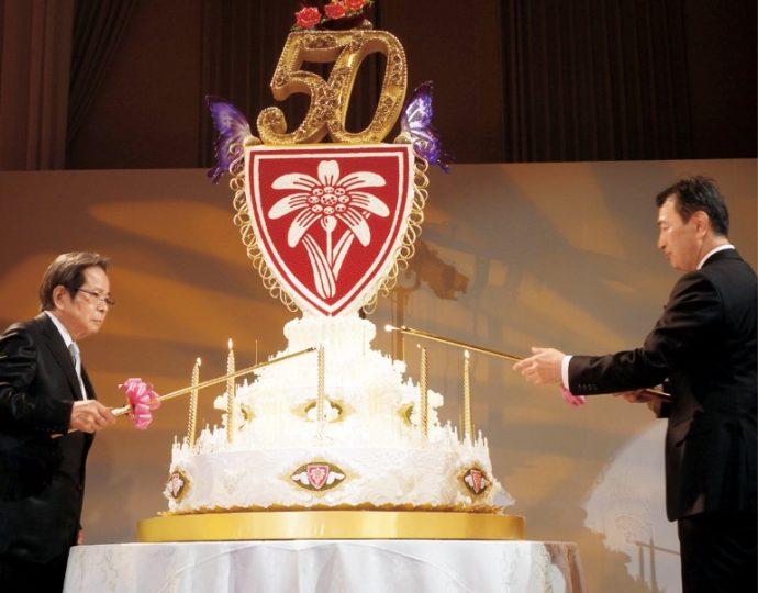 会長と社長がケーキのロウソクに点火