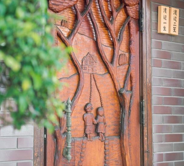 自宅の扉も木彫作品になっている。小道の先にあるのは自宅