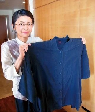 石川さんが手に持つのは館内で着用できるオリジナル作務衣